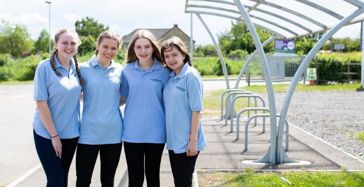 Four girls stood outside a bike shed in a line with their arms round each other