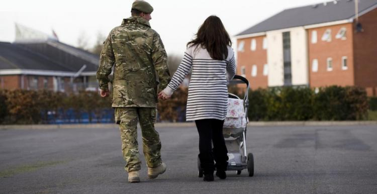 Rear view of a male soldier in uniform walking with a lady pushing a buggy