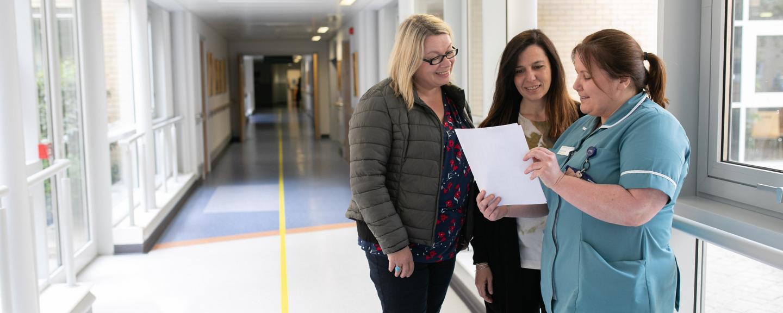 Three women talking in hospital corridor