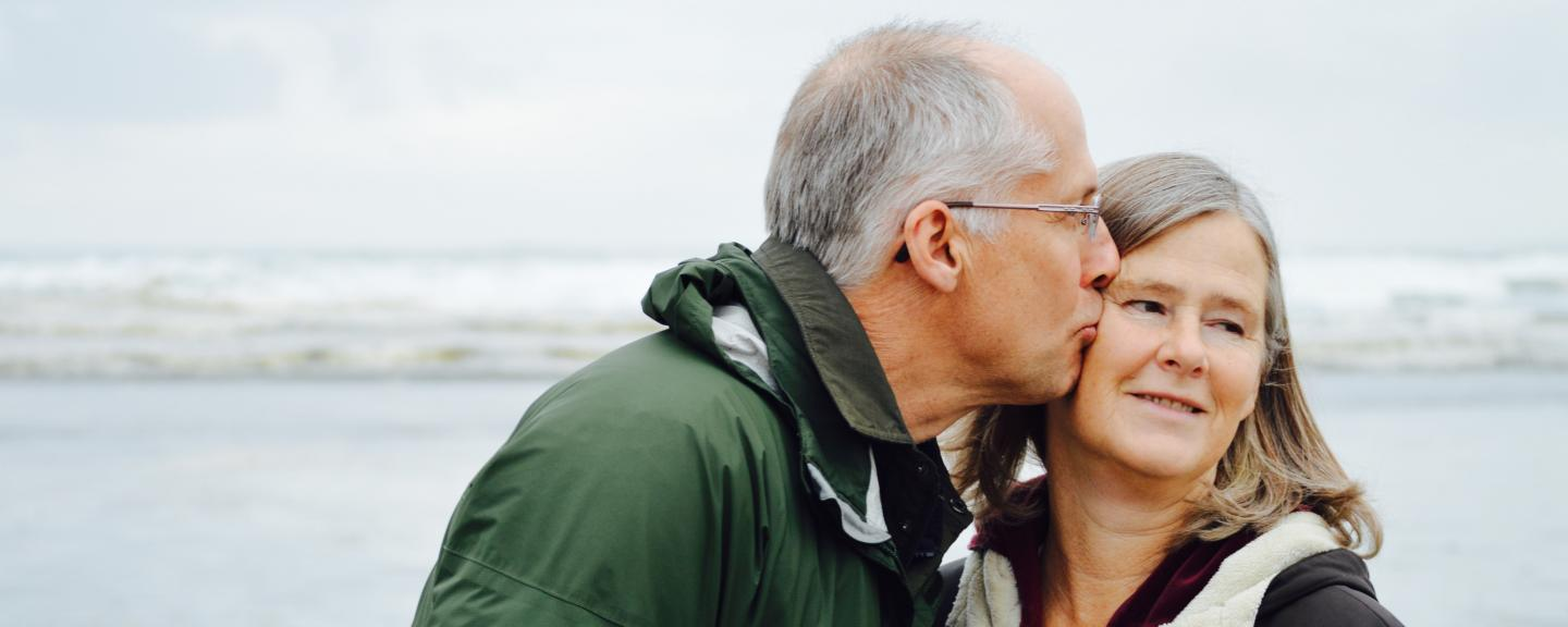 Older man kissing his female partner on the cheek at the beach