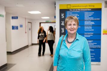 Woman standing infront of a hospital sign that shows all the different departments