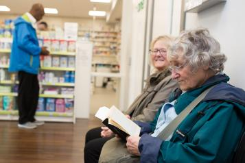 Two elderly women sitting in a pharmacy waiting for their prescription