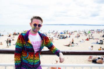 Man stood in front of the beach in a multicoloured top with multicoloured lines painted on his face