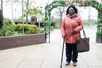Picture of a lady using a walking stick standing outside