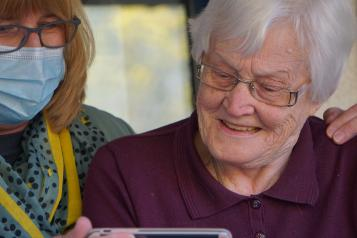 Elderly woman being helped with mobile device