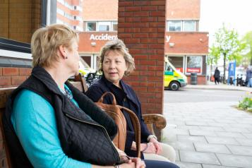 Two women sitting on a bench outside a hospital with ambulance in background