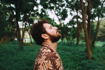 Man breathing deeply in a green space