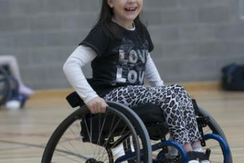 child smiling using a wheelchair
