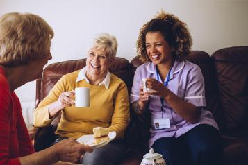 Two older women in a care home laughing with their nurse