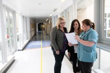 Two women talking to a nurse in a hospital corridor