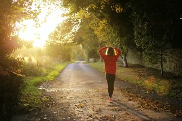 Girl wearing a red jumper walking down a leafy lane with arms outstretched