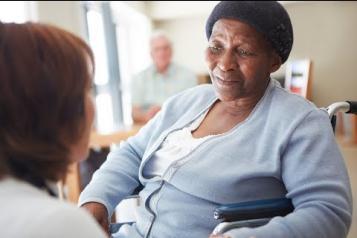 Black elderly woman in a nursing home talking to a nurse