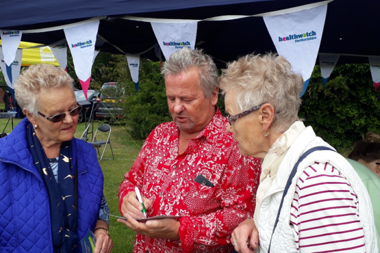 Keith Shephard speaking to two members of the public at an event