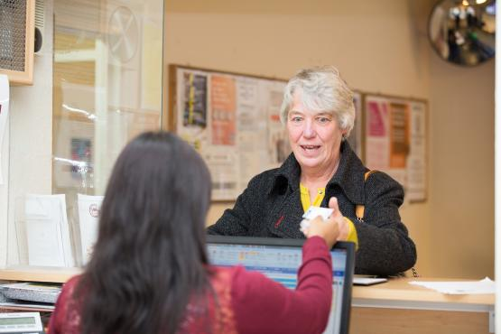 Woman handing ID card to receptionist