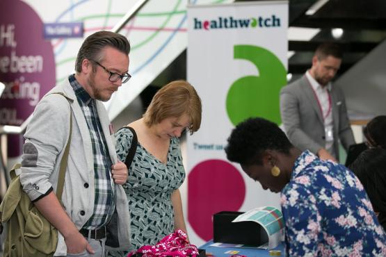 People standing around a Healthwatch stall