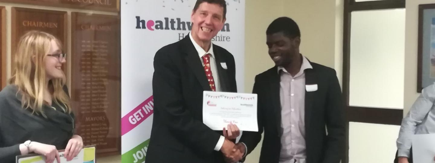 One of our volunteers being presented a certificate by the Chair