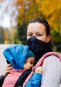 Mother wearing a face mask holding their baby